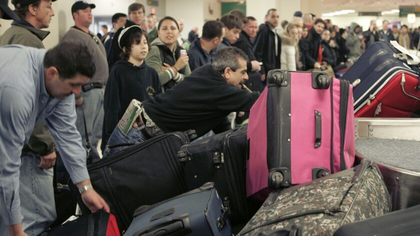 Passengers grab their suitcases on a carousel at Newark Liberty International Airport in New Jersey.