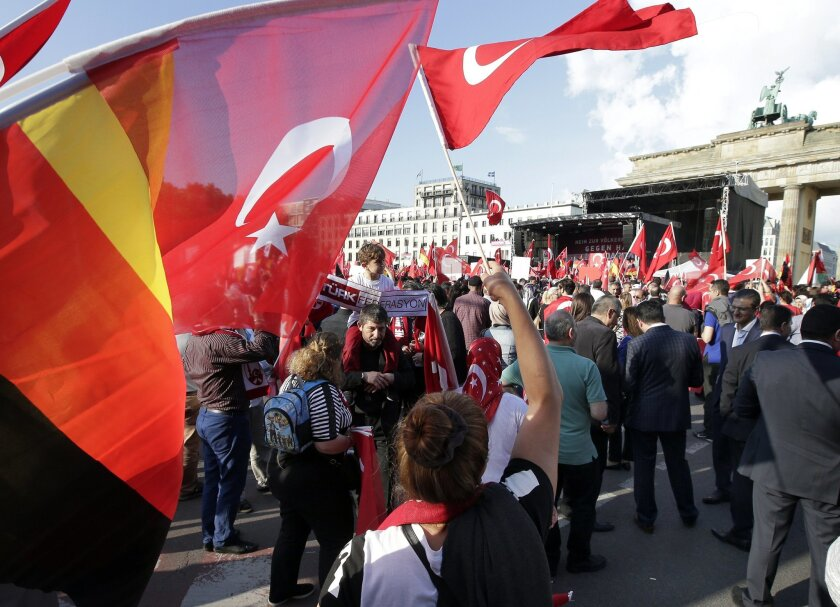 Protesters wave flags of Turkey and Germany in front of the Brandenburg gate in Berlin, Germany, Wednesday, June 1, 2016, as they demonstrate against a resolution of the German federal parliament, Bundestag, on the Armenian Genocide a century ago. Turkey's relations with Germany will be harmed if t