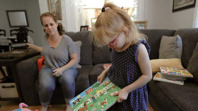Minutes before having a seizure, Brooke Adams, 5, plays with her toys with her mother, Jana at their home in Santa Rosa, Calif.
