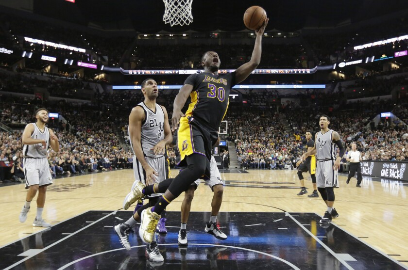 Los Angeles Lakers forward Julius Randle (30) shoots past San Antonio Spurs center Tim Duncan (21) during the first half on Friday.