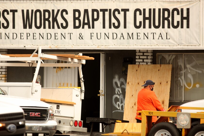 A worker cleans up the scene where authorities are investigating an explosion at the First Works Baptist Church.