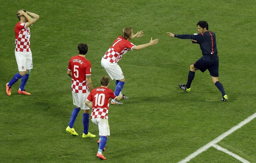 Referee Yuichi Nishimura from Japan, right, decides on penalty during the group A World Cup soccer match between Brazil and Croatia, the opening game of the tournament, in the Itaquerao Stadium in Sao Paulo, Brazil, Thursday, June 12, 2014. (AP Photo/Thanassis Stavrakis)