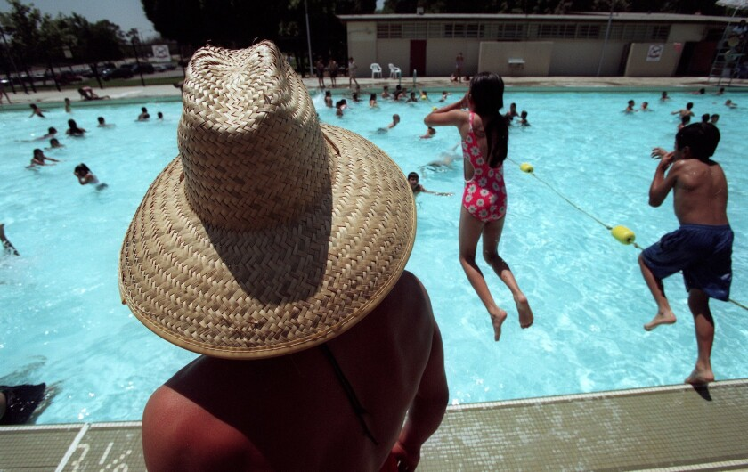 A lifeguard keeps a watchful eye on frolicking children at the Belvedere Park Community Pool on the first day of summer in 1998. The old Belvedere Park pool was demolished and replaced with a $14.8-million aquatic center.