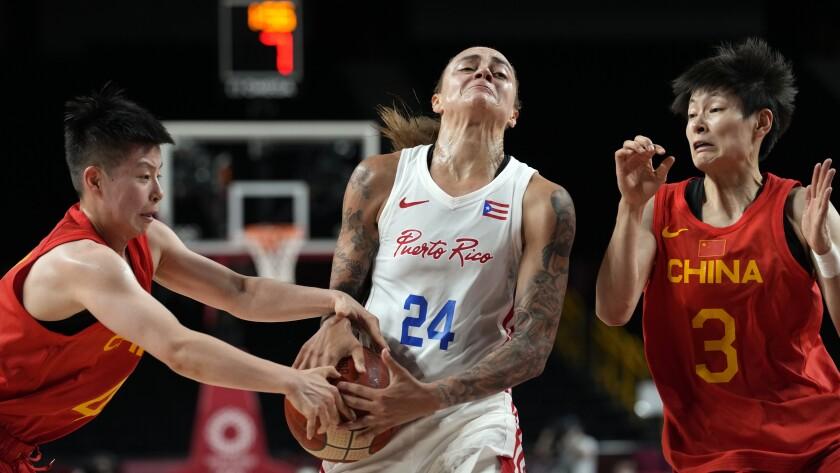 Puerto Rico's Jazmon Gwathmey (24) drives between China's Yuan Li (4) and Liwei Yang (3) during a women's basketball preliminary round game at the 2020 Summer Olympics in Saitama, Japan, Tuesday, July 27, 2021. (AP Photo/Eric Gay)