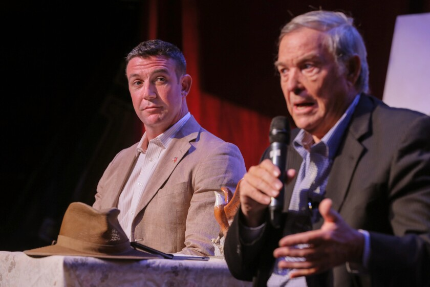 Congressman Duncan Hunter, left, listens as his father, retired Congressman Duncan Hunter speaks about border issues at their town hall meeting at the Ramona Mainstage theater.