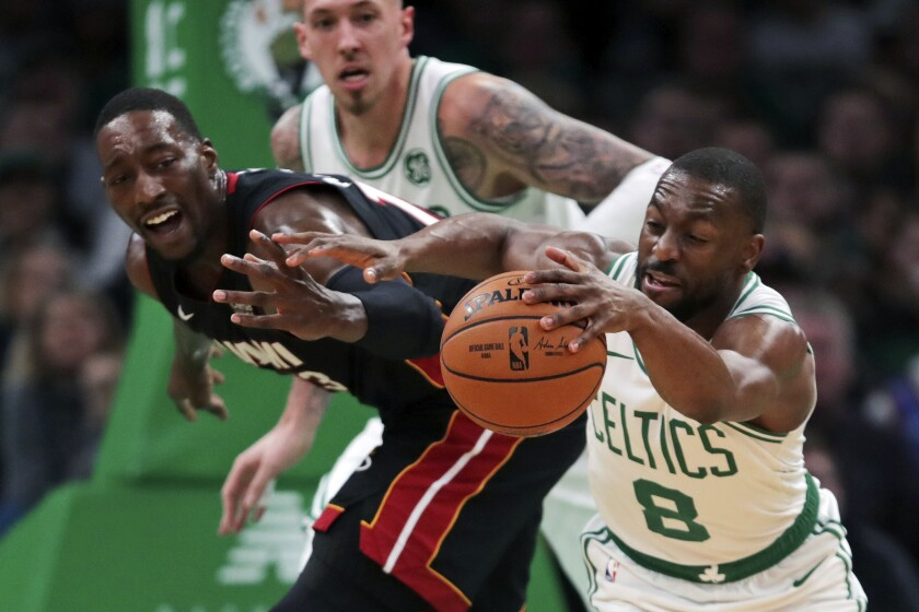 Boston Celtics guard Kemba Walker (8) steals the ball from Miami Heat center Bam Adebayo, left, during the first half of an NBA basketball game in Boston, Wednesday, Dec. 4, 2019. (AP Photo/Charles Krupa)