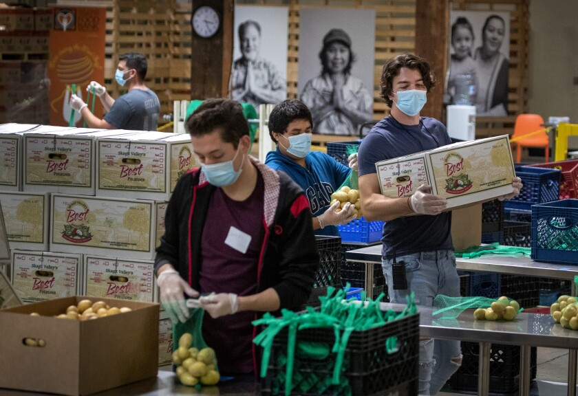 Jose Secundino and other temporary employees in face masks pack boxes at an Orange County food bank.