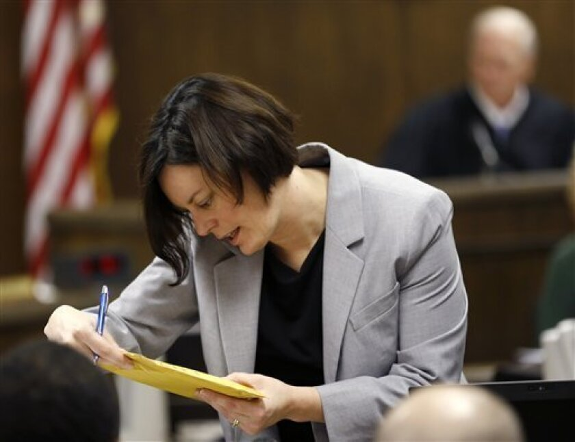 Prosecuting attorney Marianne Hemmeter, left, looks at evidence during the rape trial for 17-year-old Trent Mays and 16-year-old Ma'lik Richmond in juvenile court on Thursday, March 14, 2013 in Steubenville, Ohio. Mays and Richmond are accused of raping a 16-year-old West Virginia girl in August of 2012. Presiding Judge Thomas Lipps is visible at right. (AP Photo/Keith Srakocic, Pool)