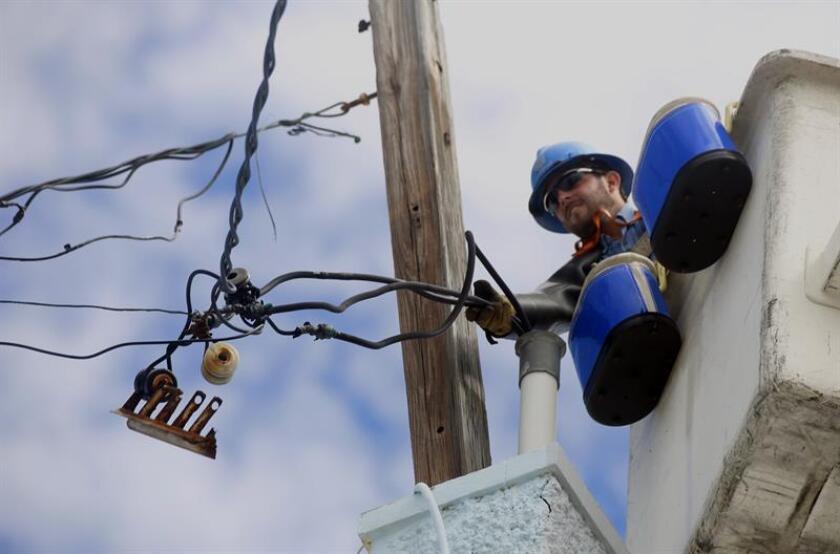 Un empleado de la empresa neoyorquina ConEdison trabaja restableciendo cables de electricidad dañados en Puerto Rico. EFE/Archivo