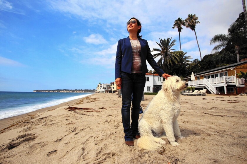 Noaki Schwartz, a spokeswoman for the California Coastal Commission, stands where a security guard asked her to leave because the beach is private -- it's not. She is photographed with a dog belonging to a local resident.