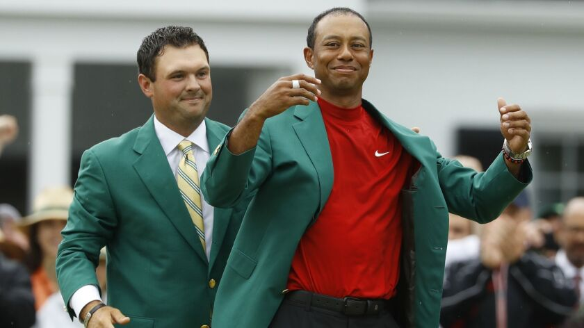 Patrick Reed helps Tiger Woods with his green jacket after Woods won the Masters golf tournament Sun