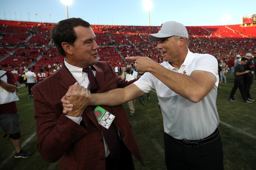 New USC Athletic Director Mike Bohn, left, greeting football coach Clay Helton after a UCLA win Nov. 23, faced withering reaction from his fan base after deciding to retain Helton.