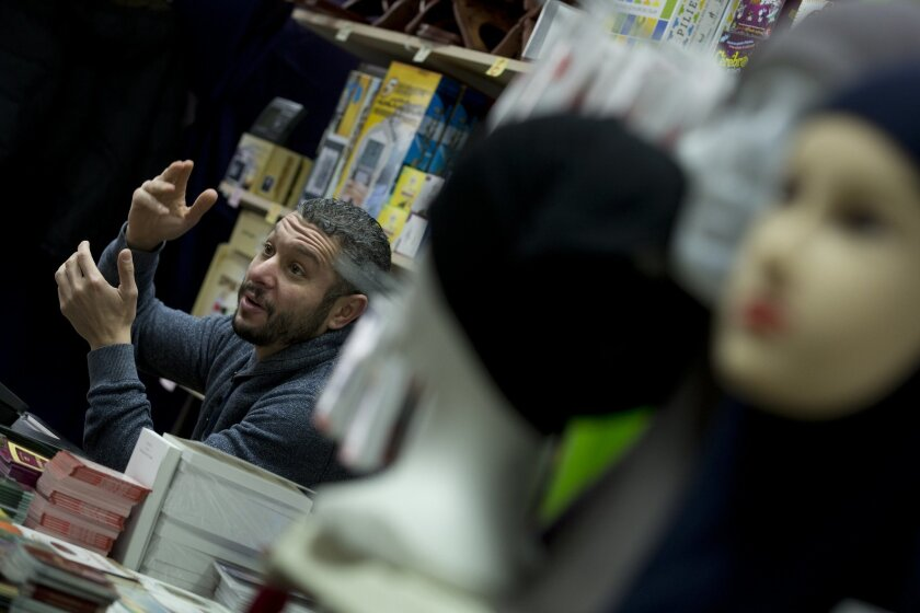 Pharred, the owner of Boutique Salam, answers questions of journalist in the Molenbeek neighborhood of Brussels, Belgium, Saturday, March 19, 2016, where fugitive Salah Abdeslam was arrested after a four-month manhunt. Abdeslam, the top suspect in last year's deadly Paris attacks, and a suspected accomplice have been discharged from a hospital in Brussels and will now face official questioning and a fast-track extradition effort. Abdeslam and his companion were injured when they were captured by police. (AP Photo/Peter Dejong)