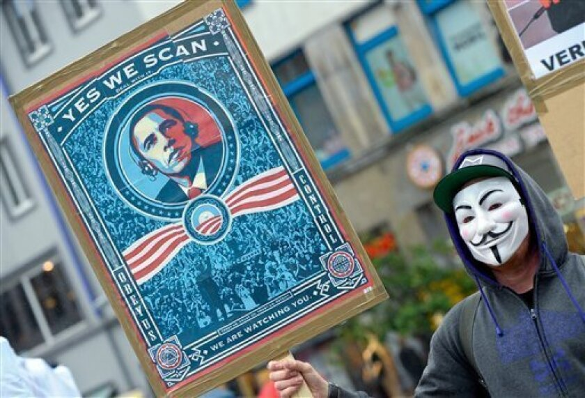 """In this picture, taken Saturday June 29, 2013, a demonstrator protests with a poster against NSA in Hanover, Germany. Germany's top justice official says reports that U.S. intelligence bugged European Union offices remind her of """"the methods used by enemies during the Cold War."""" Justice Minister Sabine Leutheusser-Schnarrenberger was responding to a report by German news weekly Der Spiegel on Sunday June 30, 2013, that claimed the National Security Agency has eavesdropped on EU offices in"""