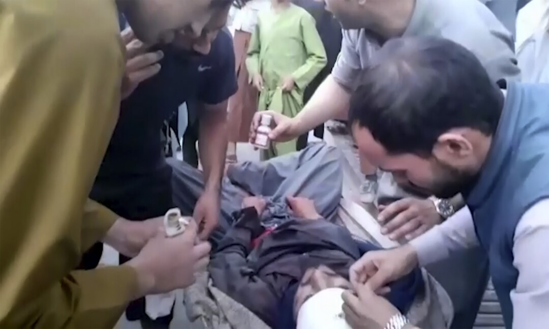 People attend to a wounded man near the site of a deadly explosion outside the airport in Kabul, Afghanistan.