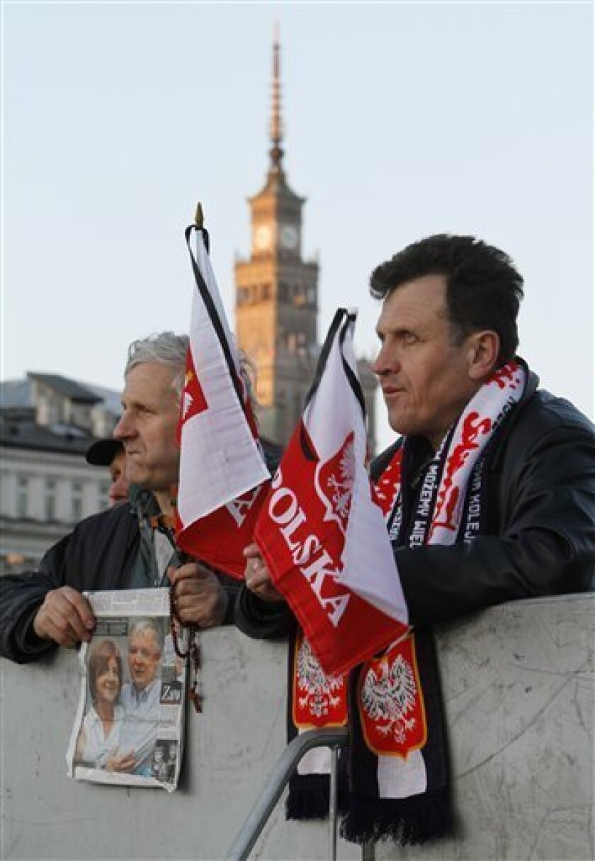 Mourners holding Polish flags and photos of the late Presidential couple wait for the beginning of a national memorial service in Pilsudski Square in Warsaw on early Saturday, April 17, 2010  in Warsaw, Poland.  Polish President Lech Kaczynski was killed in a plane crash in Russia last Saturday. (A