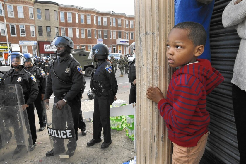 Jayden Thorpe, 5, and his mother observe what's happening Tuesday in the Baltimore neighborhood where a CVS was looted the night before.
