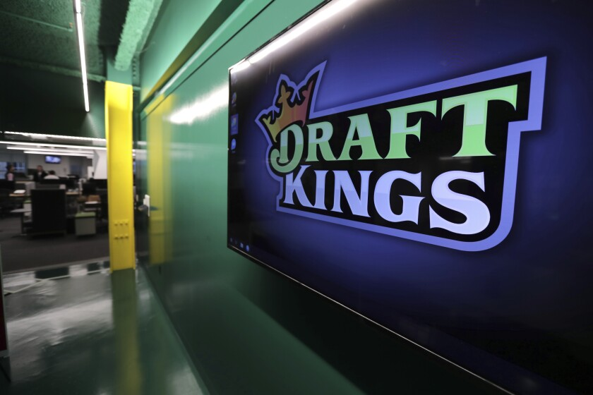 """FILE - In this May 2, 2019, file photo, the DraftKings logo is displayed at the sports betting company headquarters in Boston. DraftKings is reviewing a former """"Bachelor"""" contestant's $1 million win in an online fantasy football contest after she and her husband were accused of cheating. Jade Roper-Tolbert, who appeared in """"The Bachelor"""" and """"Bachelor in Paradise"""" television series in 2015, beat more than 100,000 entries to take the top prize in DraftKings' """"Millionaire Maker"""" contest, which involved picking a lineup of players from the NFL's four wild-card games during the weekend of Jan. 4-5, 2020. (AP Photo/Charles Krupa, File)"""