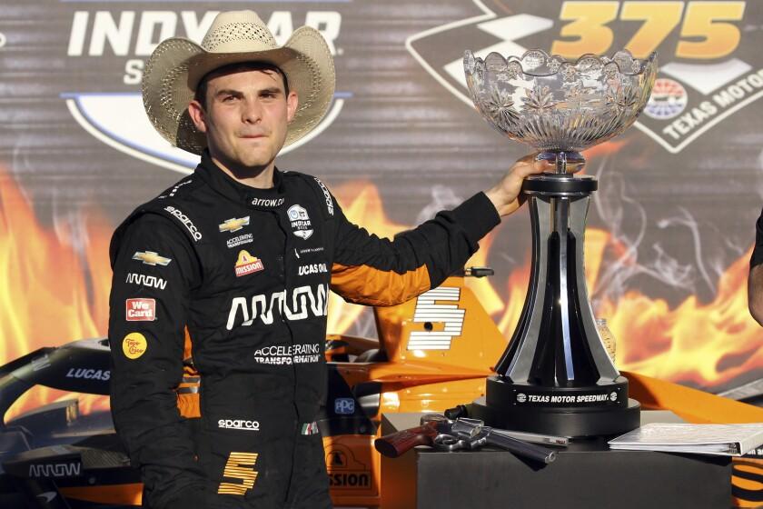 Pato O'Ward posa con el trofeo tras ganar la carrera de la IndyCar en Texas Motor Speedway