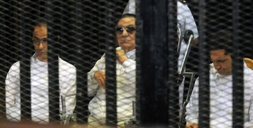 Former Egyptian President Hosni Mubarak, center, and his sons Gamal, left, and Alaa are seen behind bars during a court appearance Sunday in Cairo.