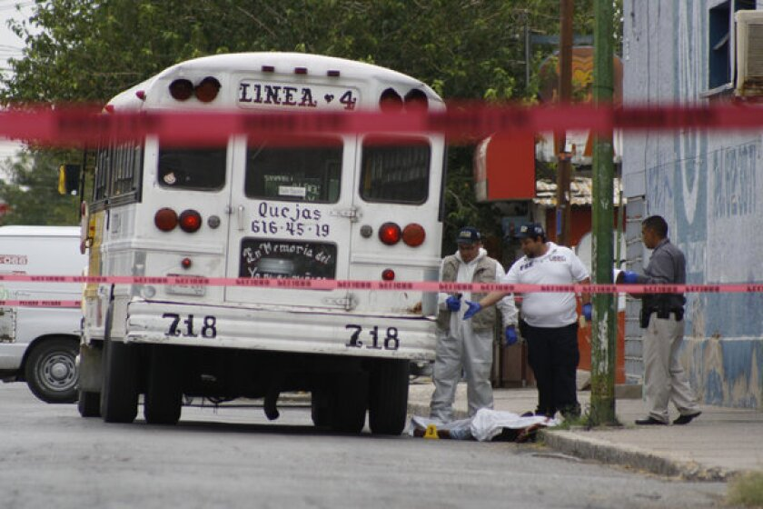 In this Aug. 28, 2013, photo, forensic experts examine the scene where a bus driver was killed in Ciudad Juarez, Mexico. Mexican prosecutors said they are investigating claims that a woman killed two bus drivers last week in this northern border city in revenge for sexual abuse of female passengers.