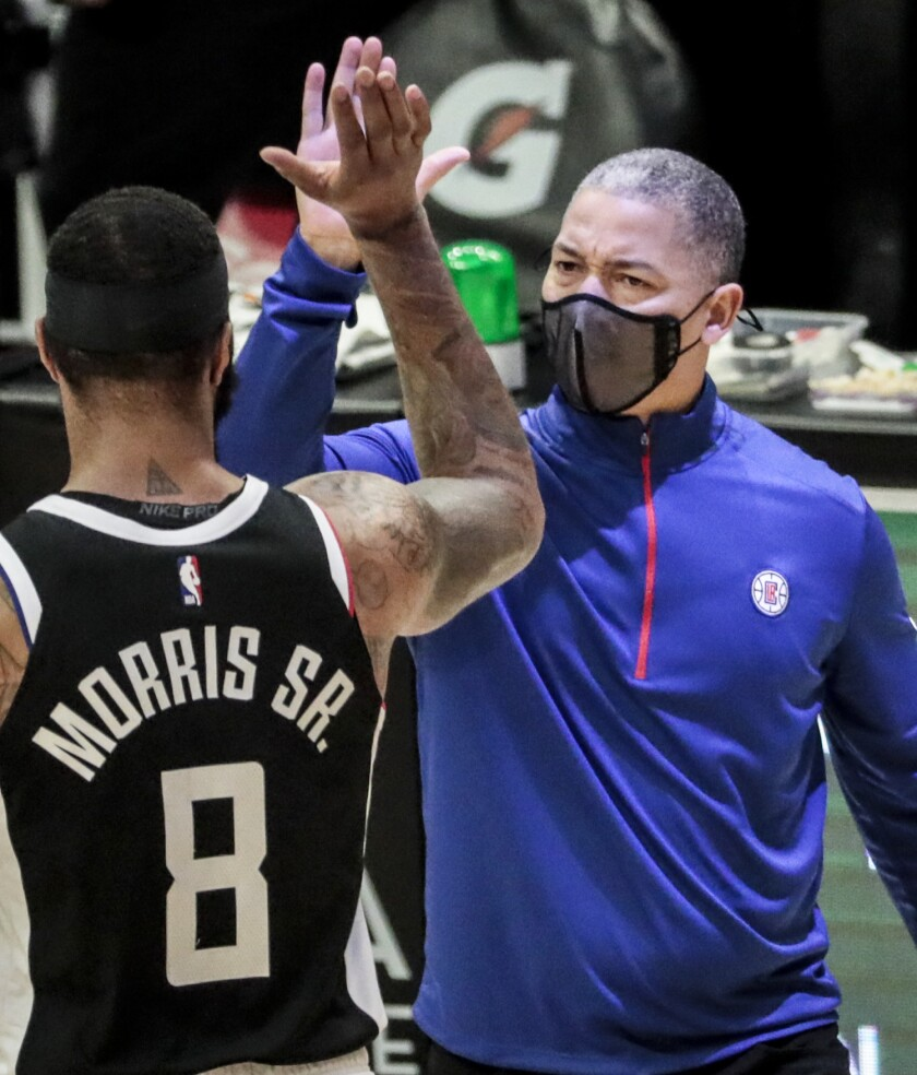 Clippers coach Tyronn Lue high-fives forward Marcus Morris as he comes off the court