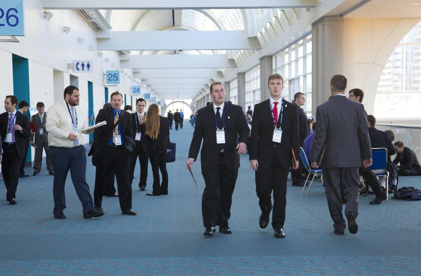 Job seekers at the Baseball Winter Meetings held at the San Diego Convention Center check in with the various job postings so that they may leave a a copy of their resume in hopes of getting a job interview.