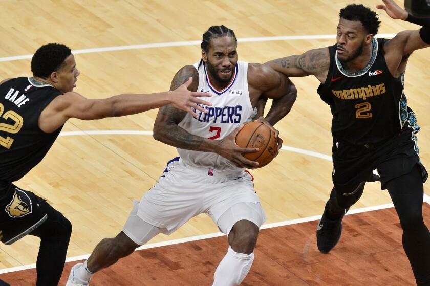 Clippers forward Kawhi Leonard drives by Memphis Grizzlies guard Desmond Bane and center Xavier Tillman.