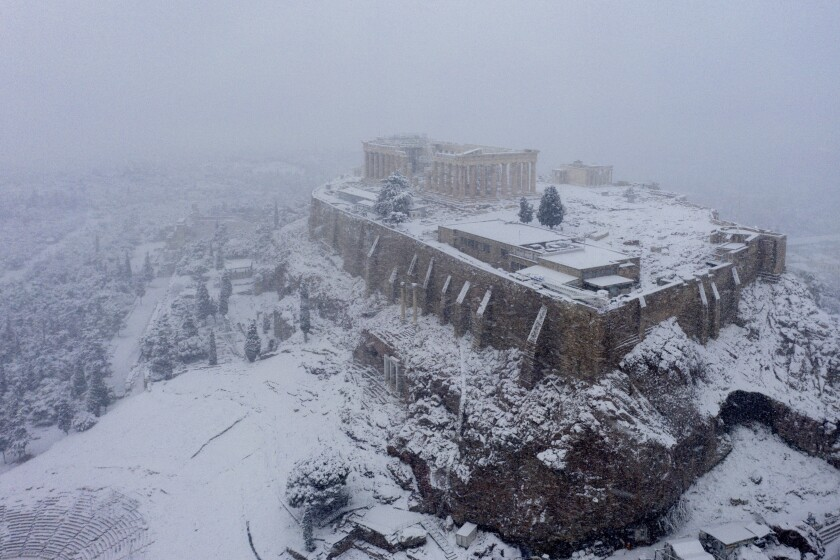 Snow covers the ancient Acropolis hill in Athens, Tuesday, Feb.16, 2021. Unusually heavy snowfall has blanketed central Athens, with authorities warning residents particularly in the Greek capital's northern and eastern suburbs to avoid leaving their homes. (Antonis Nikolopoulos/Eurokinissi via AP)