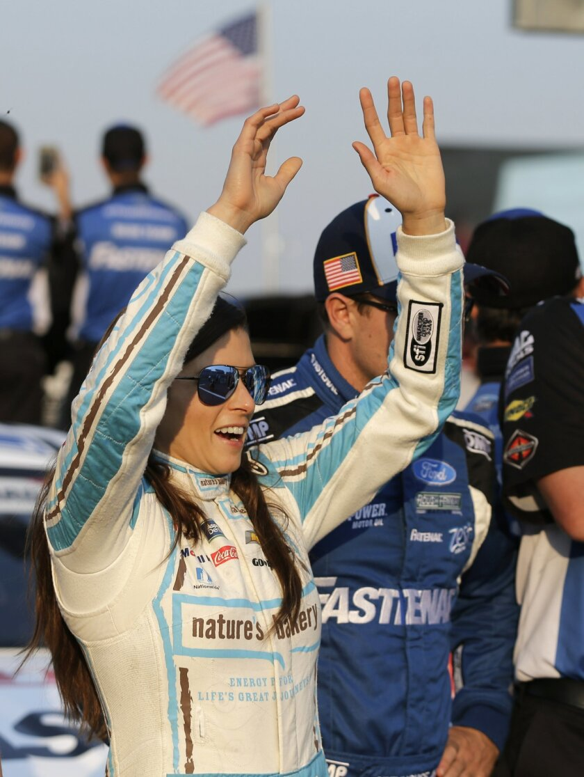 Danica Patrick cheers the finish of a charity race before qualifying for Sunday's NASCAR Sprint Cup series auto race at Charlotte Motor Speedway in Concord, N.C., Thursday, May 26, 2016. (AP Photo/Chuck Burton)