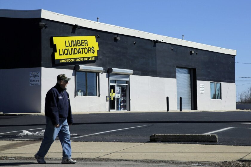 FILE - In this March 12, 2015, file photo, a man walks past a Lumber Liquidators store in Philadelphia. In a penalty announced Tuesday, March 22, 2016, Lumber Liquidators is paying $2.5 million to settle allegations that some of its products violated California's air-safety standards. (AP Photo/Mat