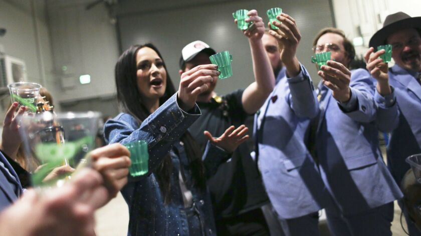 CEDAR RAPIDS, IOWA:Kacey Musgraves and her bandmates have a shot of tequila backstage before their s