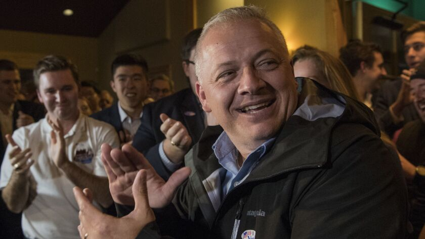 Republican congressional candidate Denver Riggleman claps with the crowd during an election party in