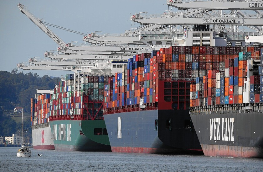 Container ships stacked high with cargo sit moored at the Port of Oakland, one of the West Coast ports that have been affected by a partial shutdown because of a labor dispute.