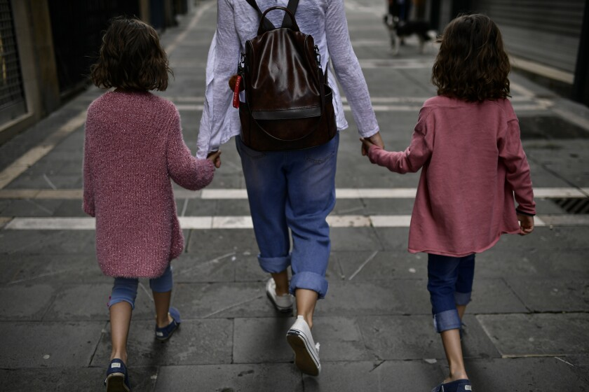 A family takes a walk in Pamplona on Sunday as children under 14 were allowed in public.
