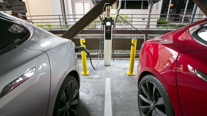 Two Tesla EVs getting charged in a public garage in Palo Alto.