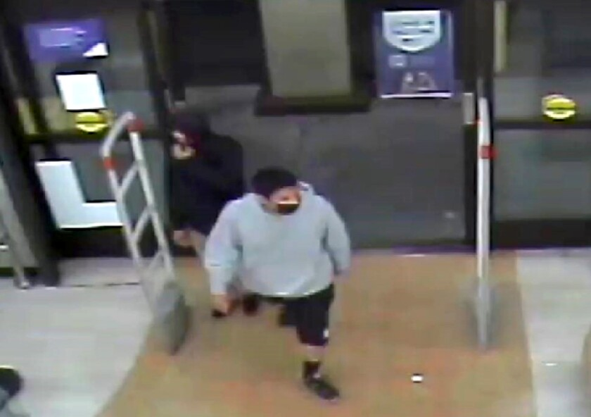 Two men are seen on a security camera at a store.