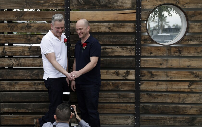 Stephan Maybroda, left, and Michael Maybroda of Delaware pose for photos after renewing their wedding vows for their 10th anniversary at the Elvis Wedding Chapel in Las Vegas on Wednesday.