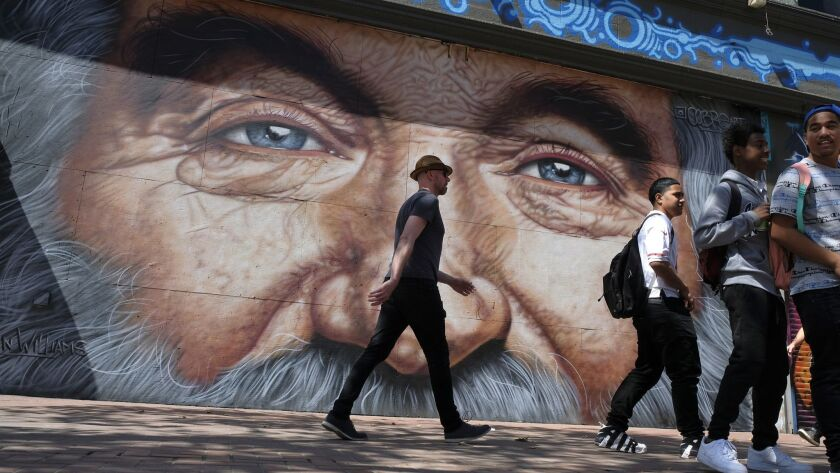 In this photo taken Wednesday, Aug. 29, 2018, people walk past a new mural of Robin Williams on Mark