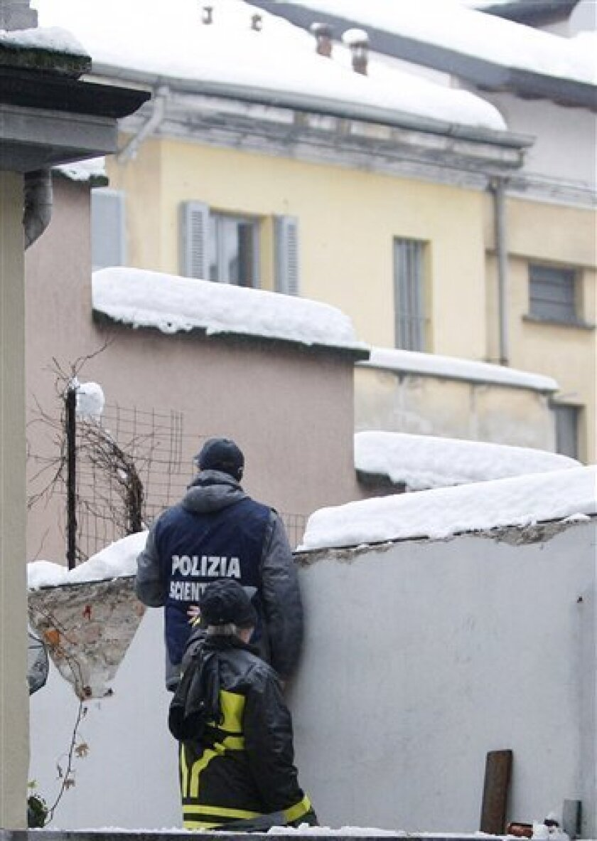 An Italian forensic police officer and a firefighter inspect a balcony next to snow-covered roofs where a 46 year-old man was crushed to death when a canopy covered in snow collapsed in downtown Milan, Italy, Wednesday, Jan. 7, 2009. Subfreezing temperatures and exceptional snowfall caused travel w