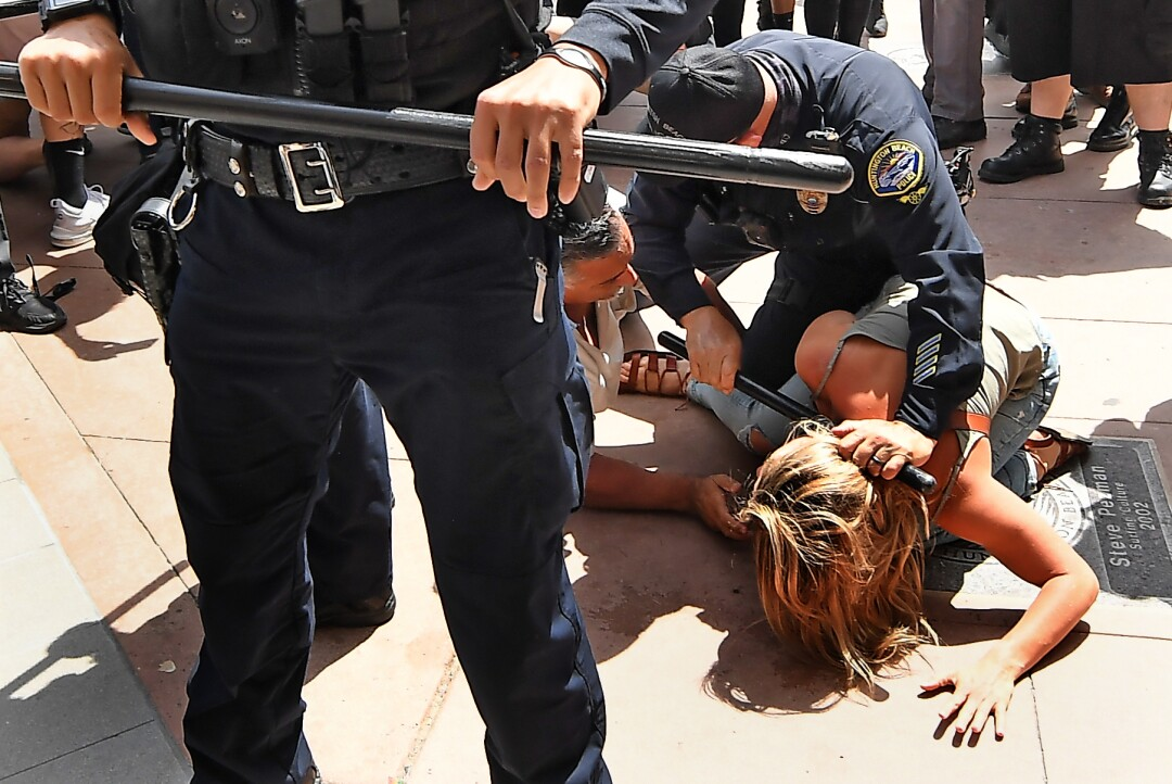 A Huntington Beach police officer grips a baton while trying to break up a scuffle between two people on the concrete