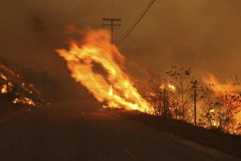 FILE - In this Nov. 9, 2018 file photo Wind-driven flames from a wildfire race up a slope and cross the road in Malibu, Calif. known as the Woolsey Fire, it has consumed tens of thousands of acres and destroyed multiple homes. Southern California Edison announced in its quarterly earnings report that its equipment probably caused the November 2018 Woolsey Fire that raged from north of Los Angeles through Malibu to the sea, killing three people and burning more than 1,600 homes and other buildings. (AP Photo/Reed Saxon,File)