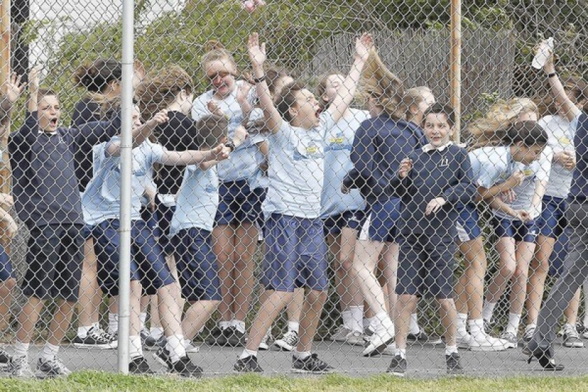 St. Joachim Catholic School students purposely stand where they know the most wind picks up from the helicopter during their school's annual helicopter golf ball drop fundraiser in Costa Mesa on Monday.