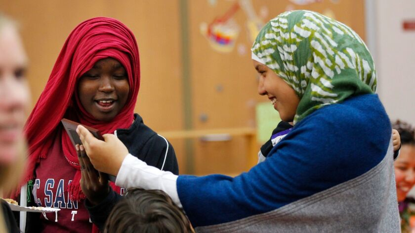 Rufaida Sulieman, 14, left, and Ayat Alchamoual, 14, look at a photo during a Thanksgiving meal for refugees and their families put on by San Diego Refugee Tutoring at Ibarra Elementary School on Tuesday, Nov. 21, 2017.