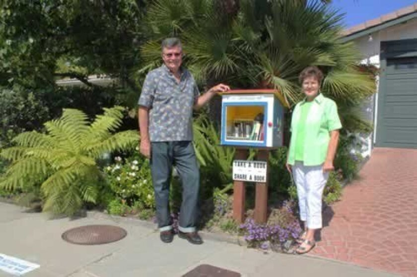 John and Karin Donaldson pose in front of the 'Little Free Library' they installed for their cul de sac on Calle Candela.