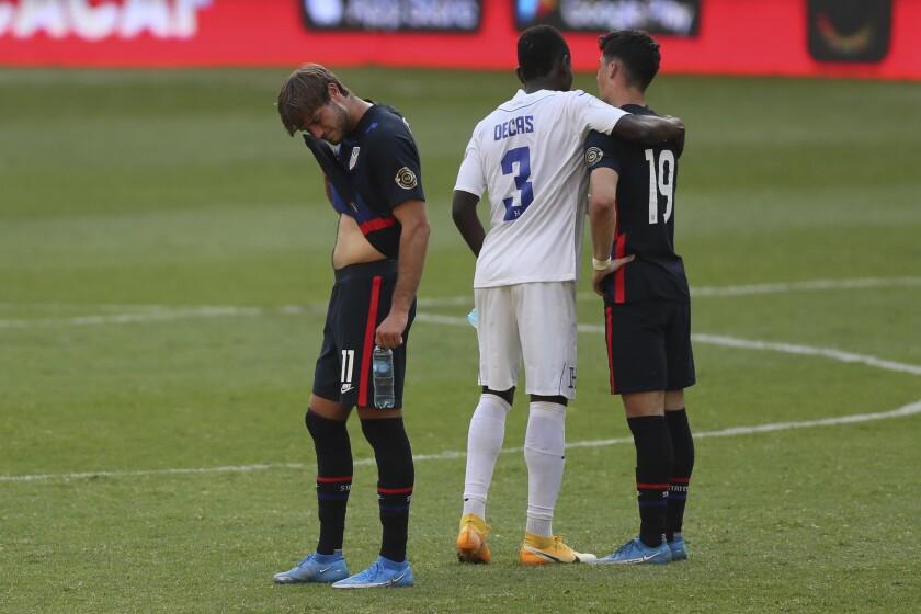 Honduras defender Wesly Decas comforts U.S. forward Sebastian Soto beside Ulysses Llanez following Honduras' 2-1 win Sunday.