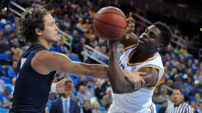 San Diego guard Mark Carbone fouls UCLA guard Aaron Holiday during the first half on Nov. 17.