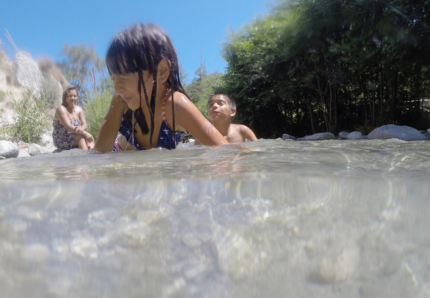 With temperatures scorching to 106 degrees, Kimberly Fuentes, 6, and her brother Anthony Villanueva, 11, of Riverside cool off in Lytle Creek, Calif.