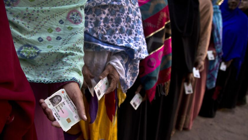 Bangladeshi women line up outside a polling station to cast their votes in Dhaka, Bangladesh, Sunday