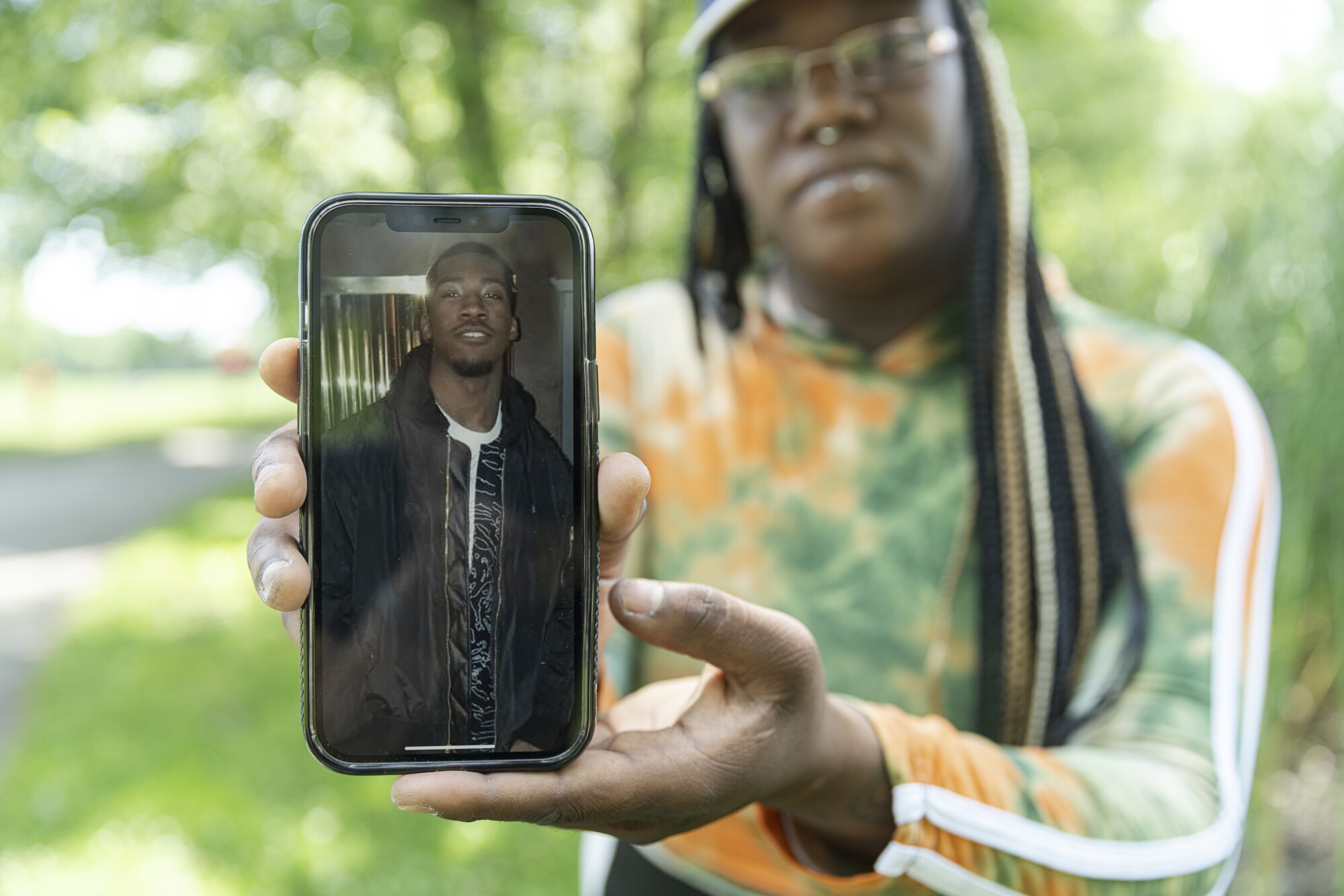 A woman holds up a phone with a photo of a man